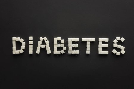 """top view of """"diabetes"""" lettering made of sugar cubes on black"""
