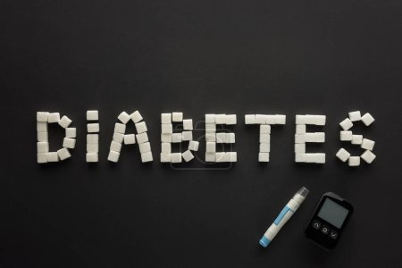 """""""diabetes"""" lettering made of sugar cubes with glucometer on black background"""