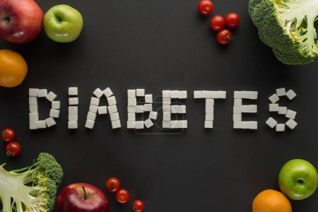 """""""diabetes"""" lettering made of sugar cubes among fruits and vegetables on black"""