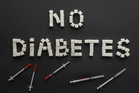 """""""no diabetes"""" lettering made of sugar cubes with insulin syringes on black"""