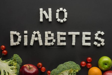 """""""no diabetes"""" lettering made of sugar cubes among fruits and vegetables on black"""