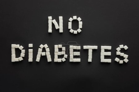"""top view of """"no diabetes"""" lettering made of sugar cubes isolated on black"""