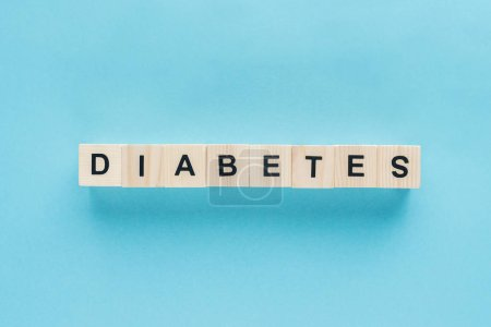 """top view of """"diabetes"""" lettering made of wooden cubes in line on blue background"""