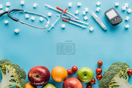 medical equipment, sugar cubes and fruits with copy space on blue background