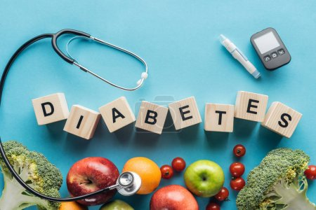 """diabetes"" lettering made of wooden cubes with medical equipment and fruits on blue background"