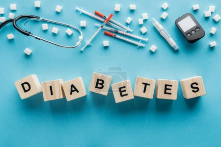 """""""diabetes"""" lettering made of wooden cubes with medical equipment on blue background"""