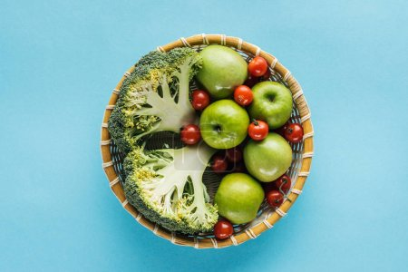 top view of vegetables and apples in wicker bowl on blue background