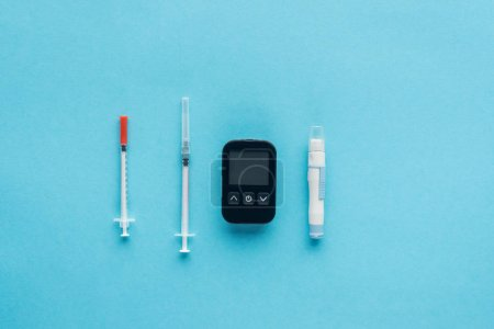 flat lay of medical equipment for diabetes control on blue background