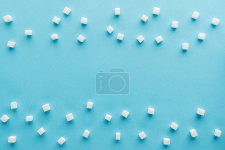 top view of white sugar cubes with copy space on blue background
