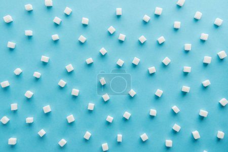 Photo for Top view pattern made of sugar cubes on blue background - Royalty Free Image