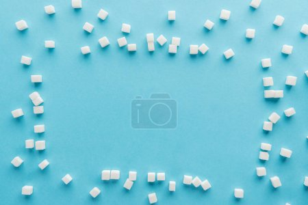 Photo for Top view of frame made with sugar cubes and copy space on blue background - Royalty Free Image