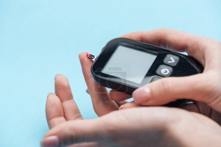 cropped view of female hands testing glucose level with glucometer on blue background