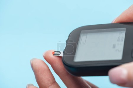 cropped view of fingers and glucometer isolated on blue background