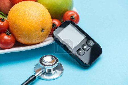 close up view of glucometer and stethoscope with tomatoes and fruits on blue background