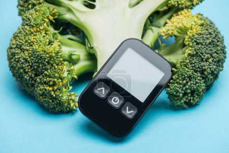 close up view of glucometer with broccoli on blue background