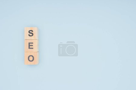 Flat lay of wooden blocks with seo lettering isolated on light blue
