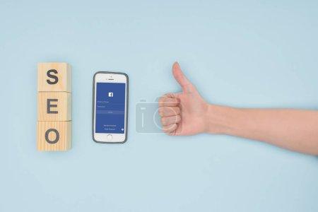 Ansicht der SEO-Managerin, die mit Facebook-App auf hellblauem Hintergrund den Daumen in die Nähe des Smartphones hebt