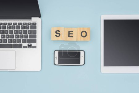 Top view of gadgets near cubes with seo lettering on light blue background
