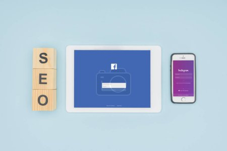 Top view of digital devices with facebook and instagram apps on light blue background