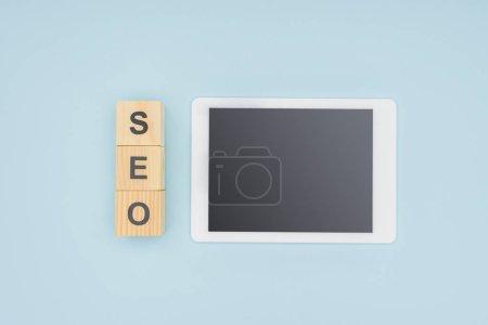 Foto de Vista superior de la tableta digital con pantalla en blanco sobre fondo azul claro - Imagen libre de derechos