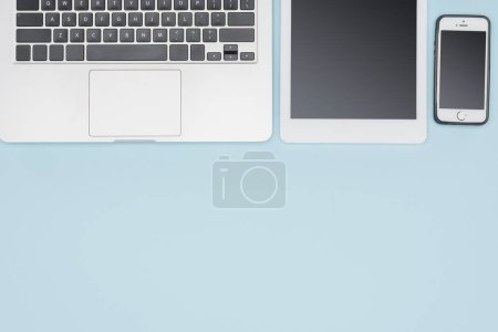 Top view of laptop, digital tablet and smartphone on light blue background