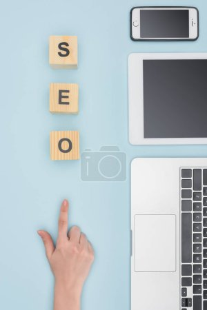 Top view of woman pointing at wooden cubes near gadgets on light blue background