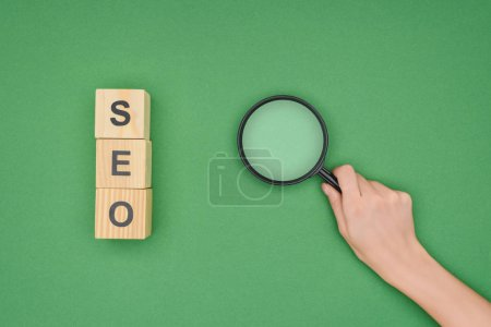 Top view of woman holding magnifier near wooden cubes on green background