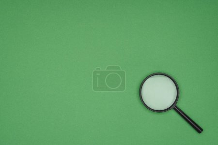 Top view of magnifying glass on green background