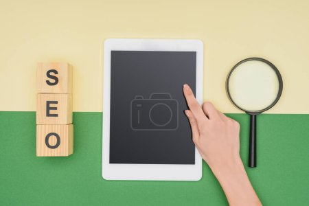 Photo for Top view of female seo manager pointing at digital tablet near magnifier and cubes - Royalty Free Image