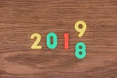 top view of date made with colorful numbers symbolizing change from 2018 to 2019 on wooden background