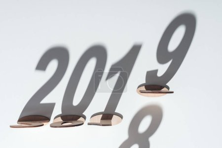 top view of wooden numbers with shadow on white background symbolizing change from 2018 to 2019