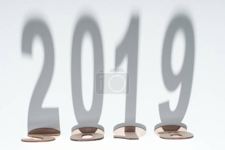 top view of wooden numbers with 2019 shadow on white background