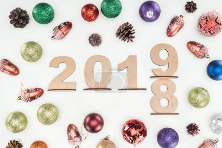 top view of wooden numbers with date symbolizing change from 2018 to 2019 with christmas decorations isolated on white