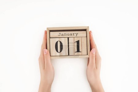 cropped view of woman holding wooden cubes with january 1st date isolated on white