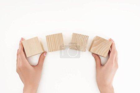 vue recadrée de femme tenant quatre blocs de bois isolés sur blanc