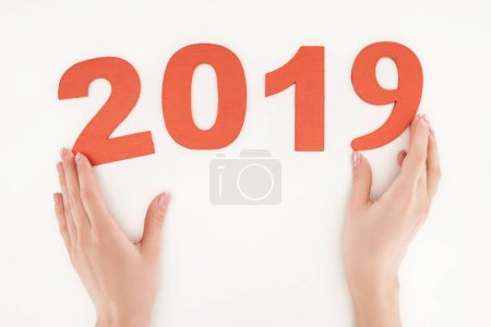 cropped view of woman adjusting 2019 date made of red numbers isolated on white