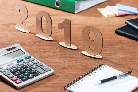 2019 date made of wooden numbers with calculator and stationery on office desk