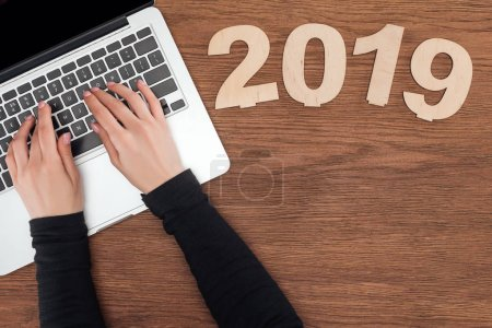 cropped view of woman using laptop at wooden table with 2019 date made of plywood