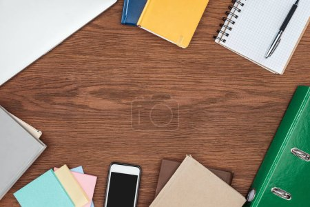 top view of wooden office desk with notebooks and smartphone with blank screen
