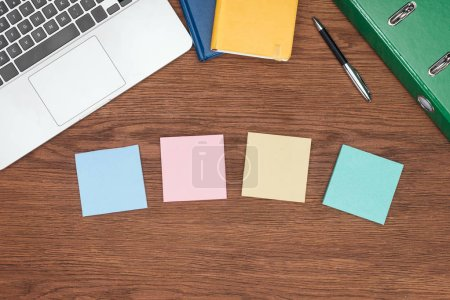 Photo for Top view of four sticky notes, laptop and office supplies on wooden desk - Royalty Free Image