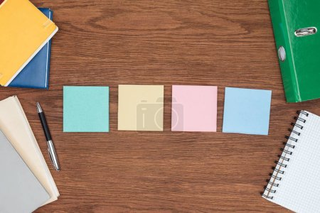 top view of  four sticky notes on wooden office desk