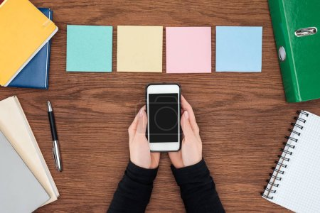 cropped view of woman holding smartphone with blank screen and four sticky notes on wooden office desk