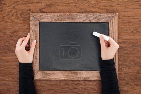 Foto de Vista parcial de la mujer que sostiene el trozo de tiza sobre pizarra vacía sobre fondo de madera - Imagen libre de derechos