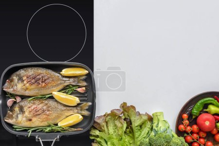top view of delicious fish with rosemary and lemon on grill and fresh vegetables on white