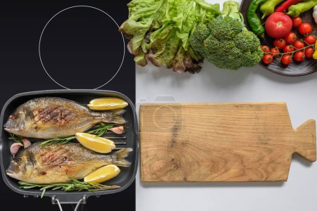 top view of wooden cutting board, fresh vegetables and delicious fried fish on grill