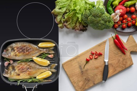 top view of delicious fried fish on electric stove and fresh vegetables with wooden cutting board and knife