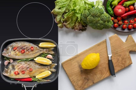 Photo for Top view of delicious fish on grill and fresh vegetables with cutting board and knife - Royalty Free Image
