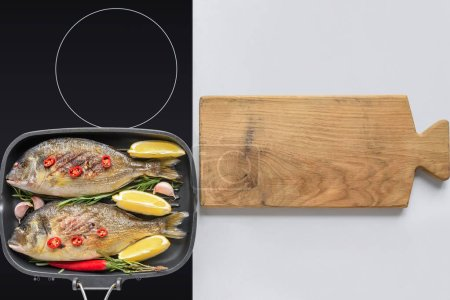 top view of delicious fried fish on electric stove and wooden cutting board