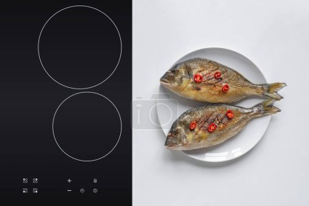 top view of delicious grilled dorado fish with cherry tomatoes on plate