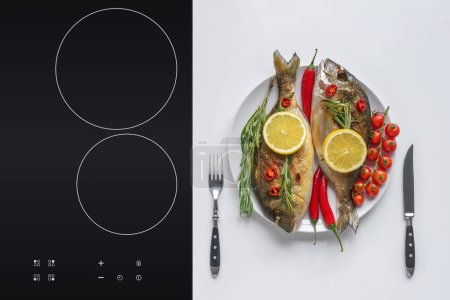Photo for Delicious fried fish with cherry tomatoes, rosemary, chili peppers and lemon on plate with fork and knife - Royalty Free Image